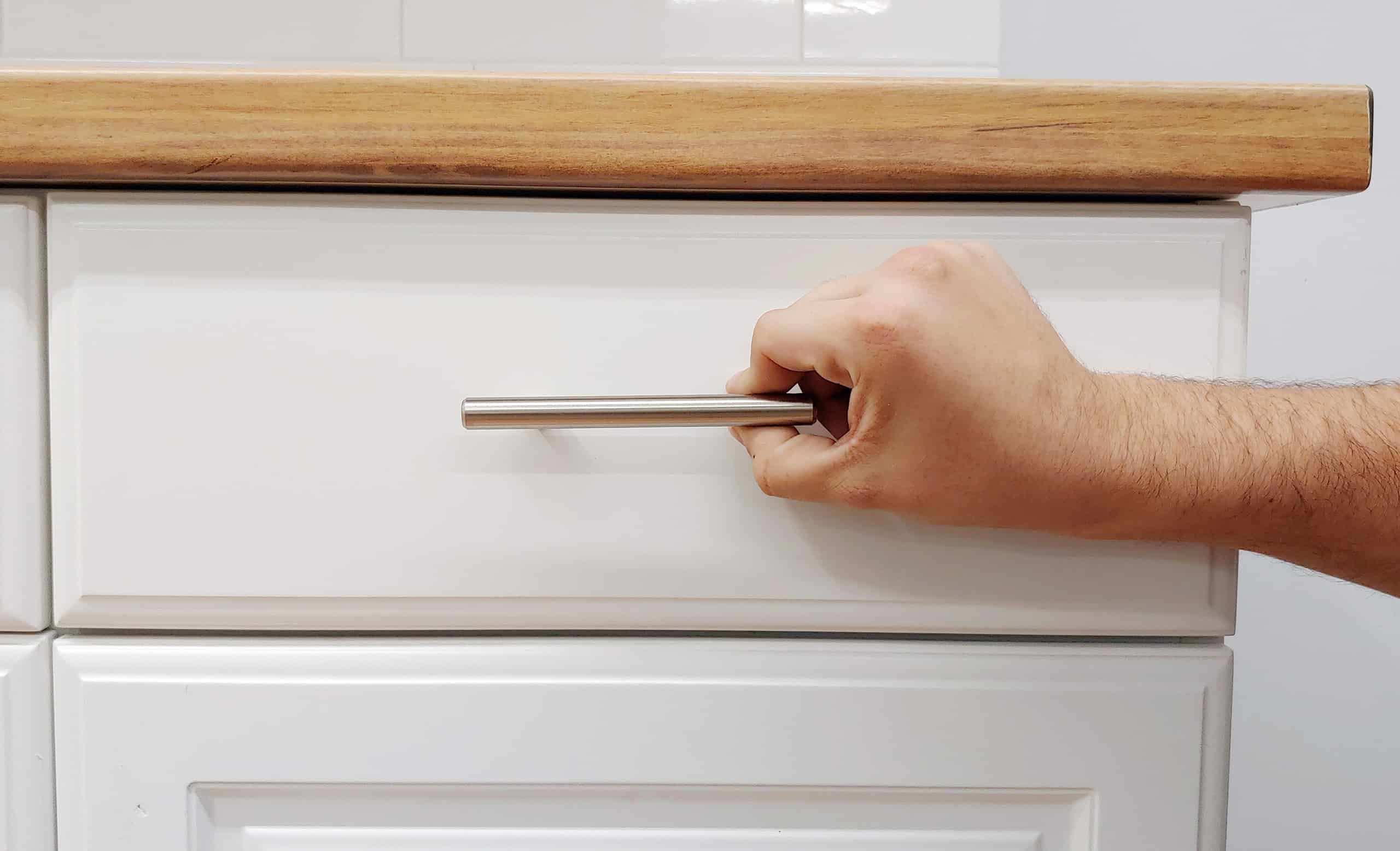Hand Placing cabinet hardware handle on drawer front