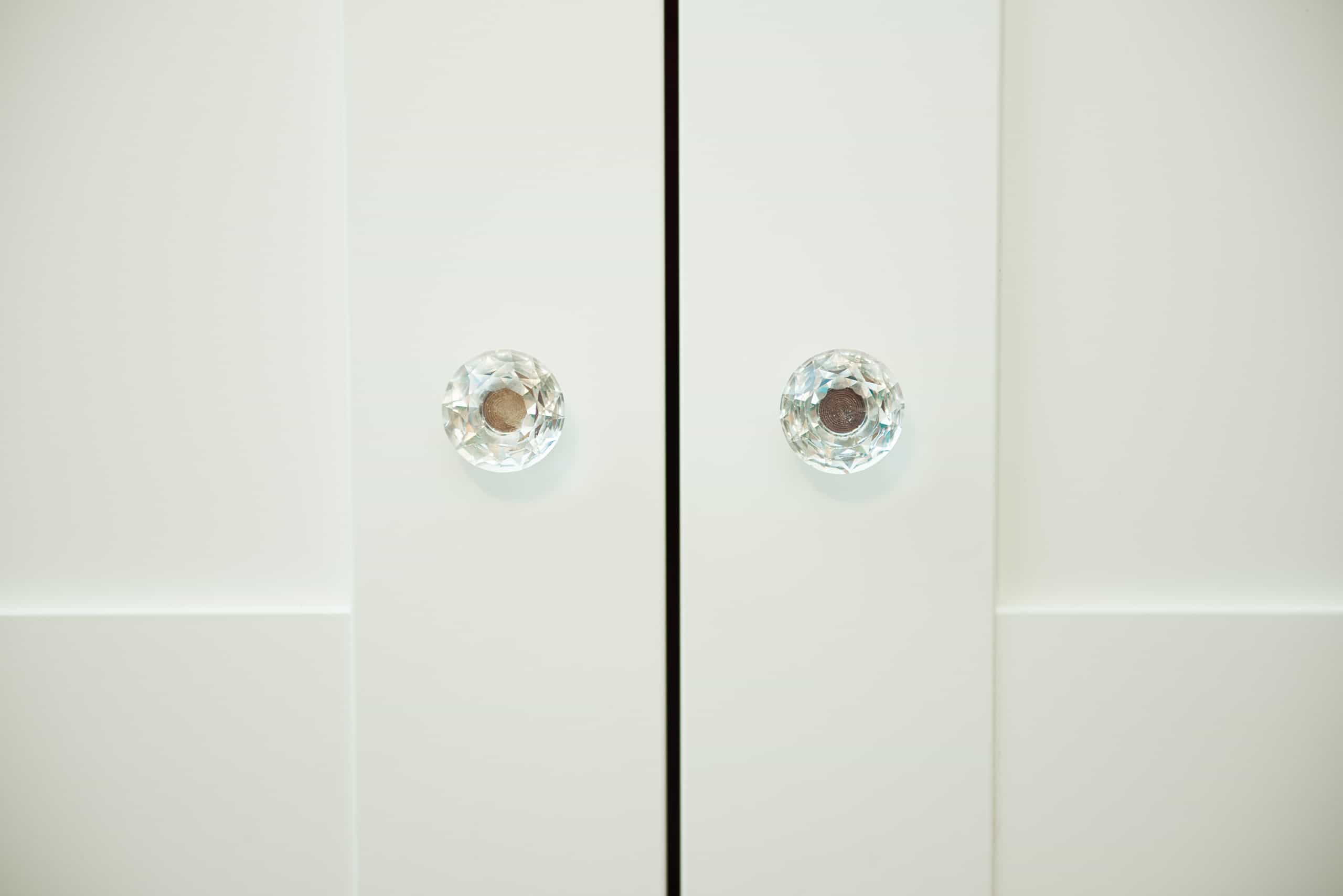 white kitchen cabinet door with trendy glass knobs