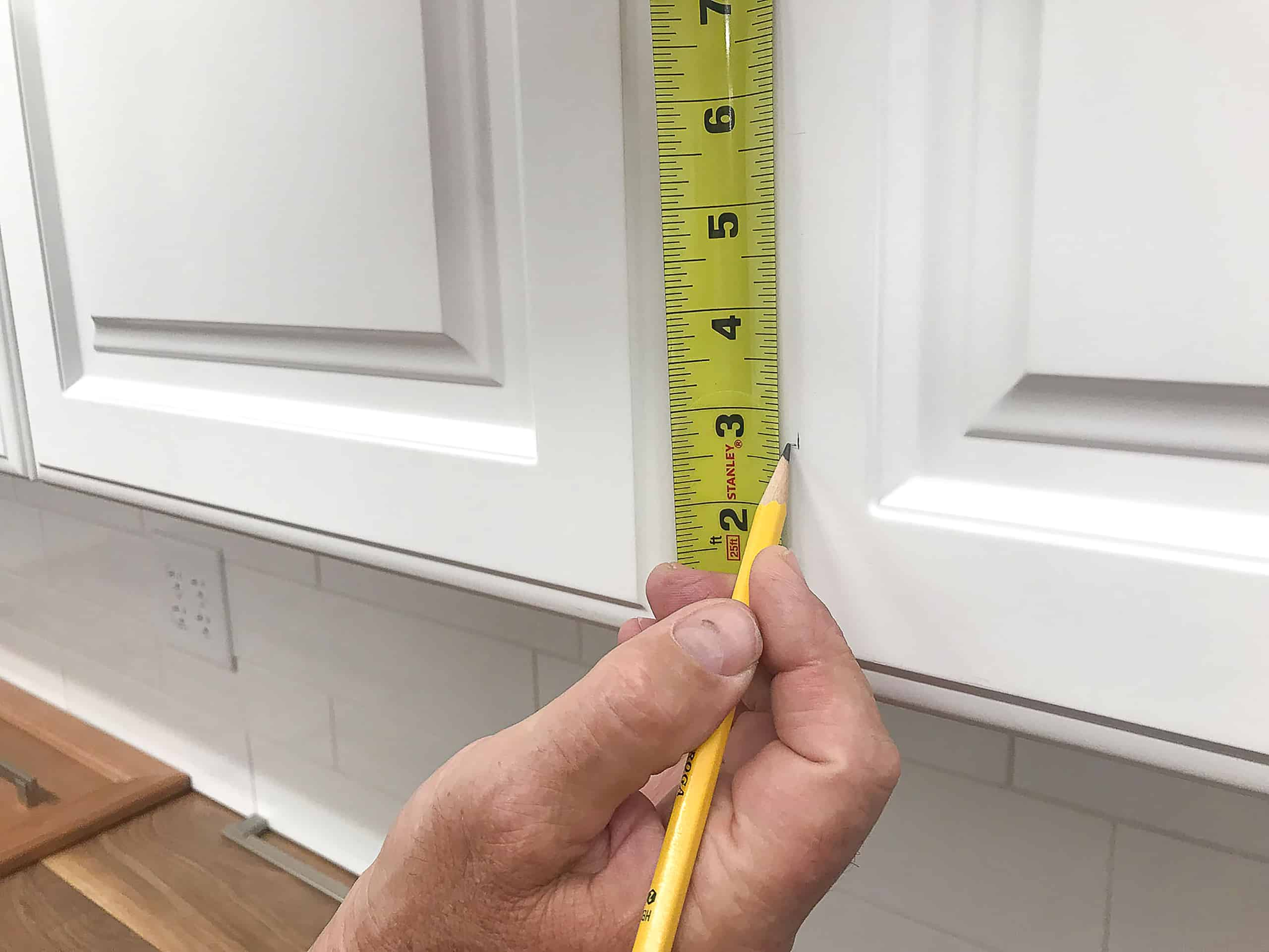Tape measure marking white kitchen cabinet door